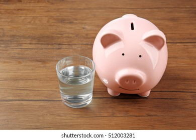 Glass of water and pig money box on wooden background