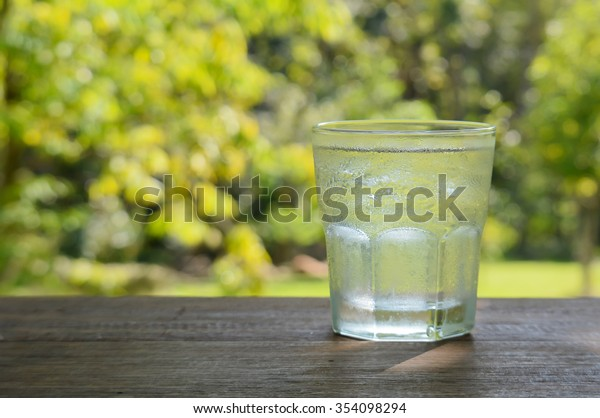 Glass water placed on wooden table,blur green background.focus glass.