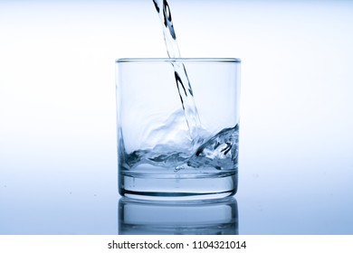 Glass of water with pouring from the bottle, studio shot