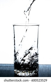 Glass with water, pouring water, ice, spray