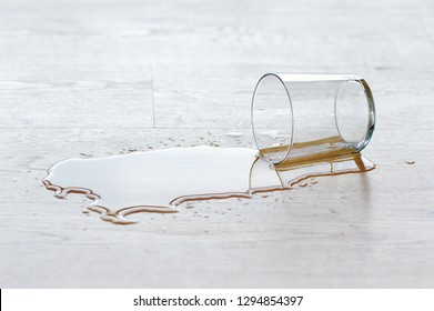 glass of water spilled on wooden floor