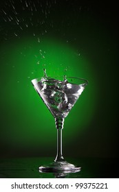 glass of water with splash on gradient green and black