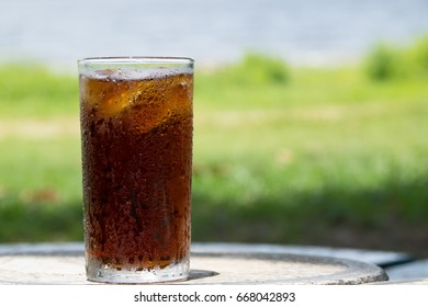 A glass of water with steam on a green background looks refreshing.