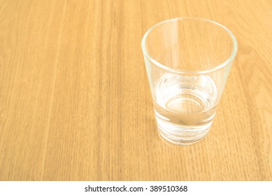 glass of water in the table color oak