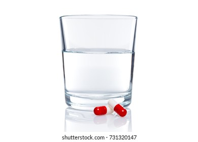 Glass of water and two pills isolated on white background with clipping path.