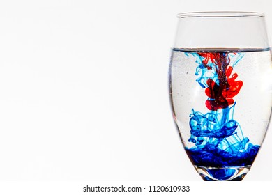 Glass of water with vivid colors of blue and red flowing through the liquid