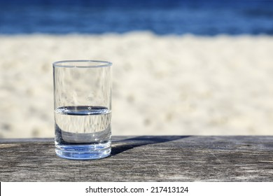 Glass of water which is half-full stands on a wooden table which stands on the sand beach by the sea
