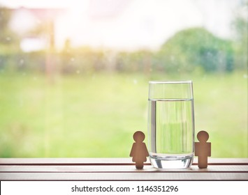 glass of water with wooden woman and man. Space for text