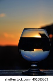 Glass of water/white vine with reflections of city and view to beautiful sunset. Selective focus.