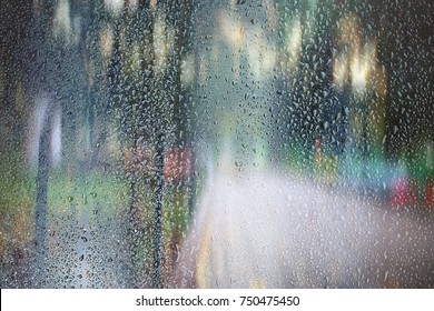 glass wet autumn background, rain in the park glass wet surface with reflection, rain drops on the drenched window glass, background window in the autumn park, autumnal rainy landscape blurred