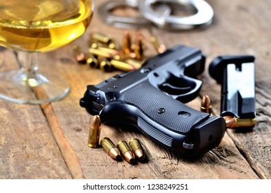 Glass of whiskey, 9mm pistol, handcuffs, bullets and magazine on old wooden table