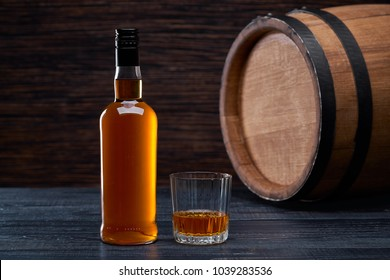 Glass of whiskey background of barrel and  old table of wood.Whiskey drink.