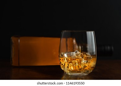 Glass of whiskey and it's bottle with dark background