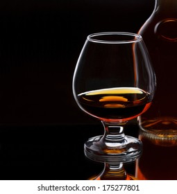 Glass of whiskey with bottle, on dark background with place for text, selective focus on the glass