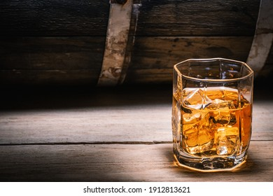 Glass of whiskey or brandy with ice close-up on the background of a wooden barrel of an alcoholic drink. Whiskey brandy scotch cognac strong alcoholic drinks.