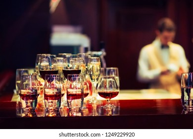a glass of whiskey, brandy on the bar. A glass with red wine on the bar. a glass of red wine.