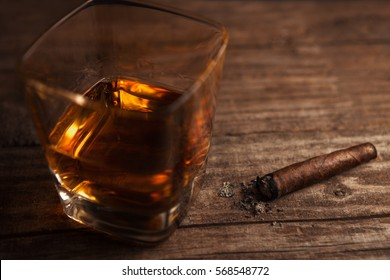 Glass with whiskey and cigar with ashes on wooden table