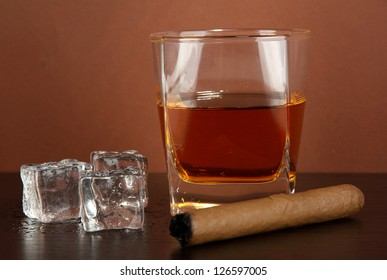 Glass of whiskey and cigar on brown background