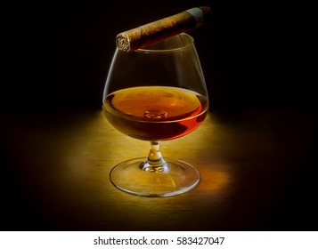 A glass of whiskey with a cigar on a dark background.