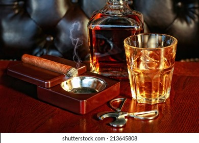 A glass of whiskey and cigar on a wooden table