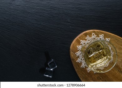 Glass of whiskey and cigar with snack on the stone table. Top view with copy space