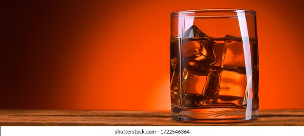 A glass of whiskey or cognac and ice cubes.