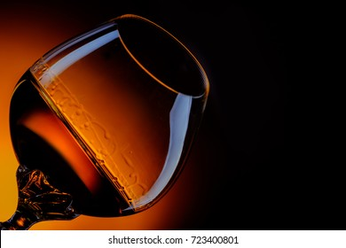 Glass with whiskey or cognac on black background with space for text.