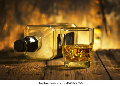 A Glass of whiskey and empty Bottle of whiskey on a wooden background