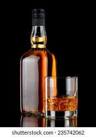 Glass with whiskey and a full whiskey bottle