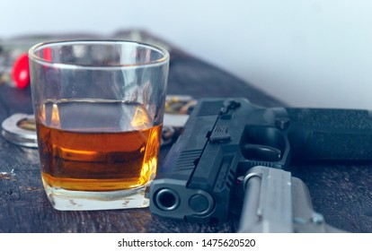 Glass of whiskey and gun.Concept of crime and alcohol relation.