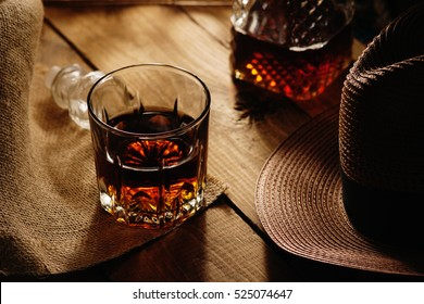 Glass of whiskey and hat