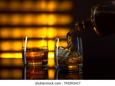 Glass of whiskey with ice and bottle on a yellow background.