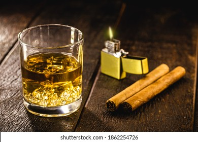 glass of whiskey with ice and cigar, with zippo lighter in the background. Smoking and relaxation concept, expensive drink