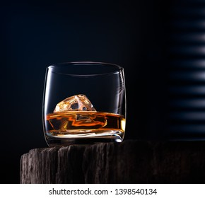 Glass of whiskey with ice cube on the wooden table with cold blue dark background