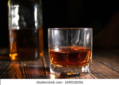 Glass of whiskey with ice cubes, a bottle on a wooden table. An old tabletop with light and a glass of strong drink.