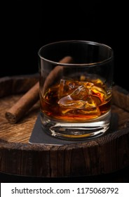 Glass of whiskey with ice cubes and cigar on top of wooden barrel. Cognac and brandy drink