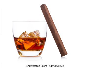 Glass of whiskey with ice cubes and cigar on white background. Cognac and brandy drink
