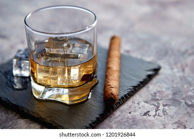 Glass of whiskey with ice cubes and cigar placed on top of stone serving plate. Stone marble background.