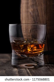 Glass of whiskey with ice cubes next to wooden barrel. Cognac and brandy drink