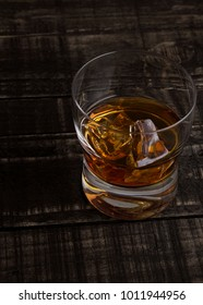 Glass of whiskey with ice cubes on wooden table background top view