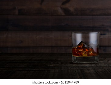 Glass of whiskey with ice cubes on wooden table background