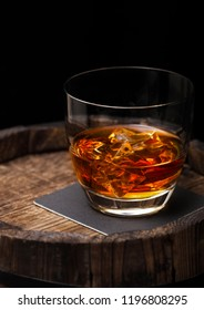 Glass of whiskey with ice cubes on top of wooden barrel. Cognac and brandy drink
