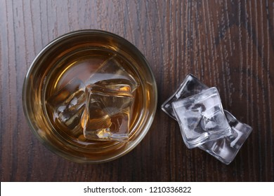 Glass with whiskey and ice cubes on wooden background. Top view
