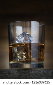 Glass with whiskey and ice cubes on brown background