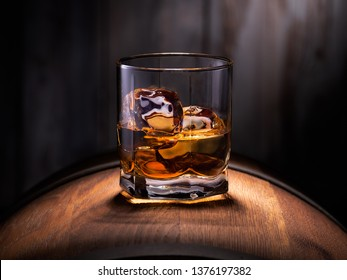 Glass of whiskey with ice cubes on the wooden barrel with wooden background
