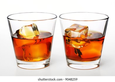 glass of whiskey with ice cubes on white background