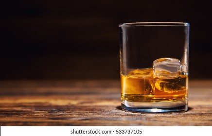 Glass of whiskey with ice cubes served on wooden planks. Vintage countertop with highlight and a glass of hard liquor