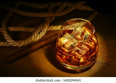 Glass with whiskey, ice cubes and smoking pipe on wooden background.