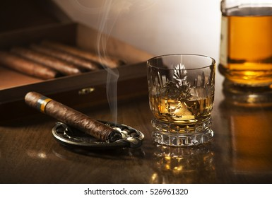 Glass of whiskey with ice cubes and smoking cigar on wooden table