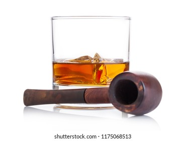 Glass of whiskey with ice cubes and vintage smoking pipe on white background. Cognac and brandy drink